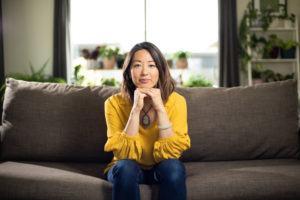 dr jin ong portrait at home on the couch pyschosomatic emotional therapy coach